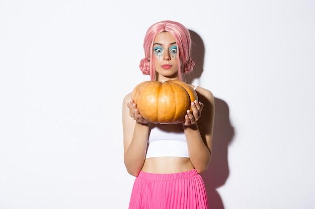 ピンクのかつらとハロウィーンのメイクで、白い背景の上に立って、大きなカボチャに興奮しているかわいい女の子の画像