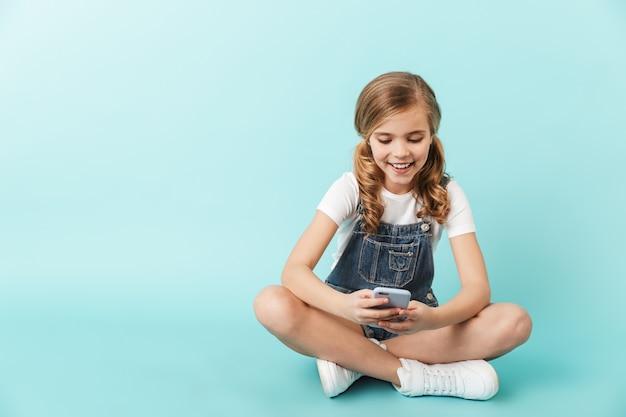 Изображение довольно счастливой молодой маленькой девочки, позирующей изолированной над синим wallusing мобильного телефона в чате.