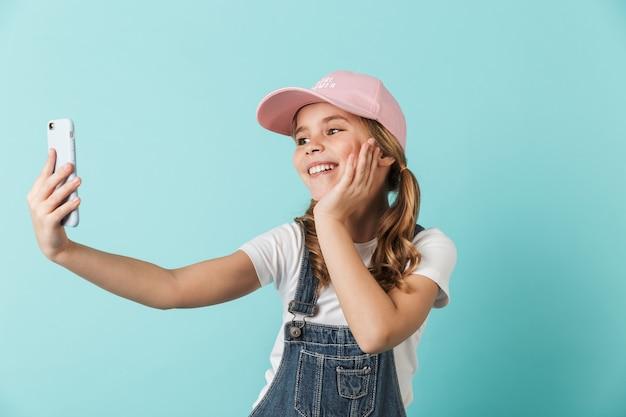 Изображение довольно счастливой молодой маленькой девочки, позирующей изолированной над синей стеной, используя мобильный телефон, принимает селфи.