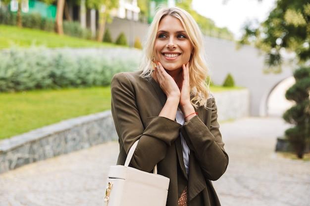 공원을 걷는 동안 재킷을 입고 가방을 들고 예쁜 여자 20 대의 이미지