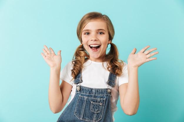 Изображение довольно молодой маленькой девочки позирует изолированной над синей стеной.