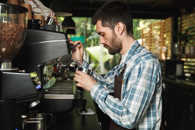 屋外のカフェや喫茶店で働いているときにコーヒーを作るエプロンを着ているプロのバリスタ男性の画像