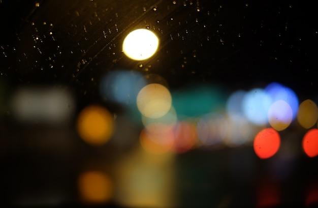 도시에서 밤에 창에 빗방울의 이미지