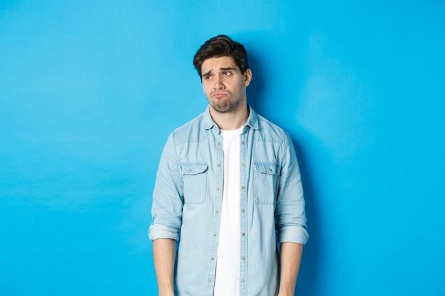 青い背景に立って、左を見て、眉をひそめ、動揺しているカジュアルな服装で気が進まない悲しい男の画像