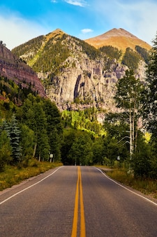 Изображение дороги в горах, ведущей к большим вершинам