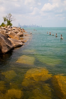 Изображение скалистого берега озера и все еще синего озера в пасмурный день с белыми деревянными столбами в воде