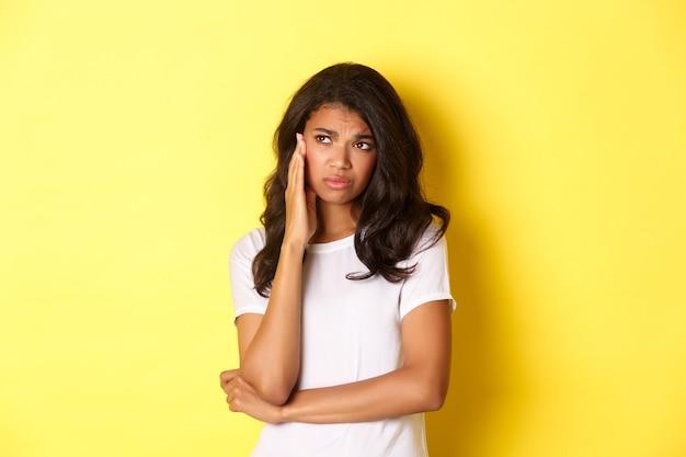 슬프고 우울한 아프리카계 미국인 소녀의 이미지는 왼쪽에 화가 난 것처럼 보이고 삐걱거리며 노란색 배경 위에 서 있는 동안 불안해합니다.
