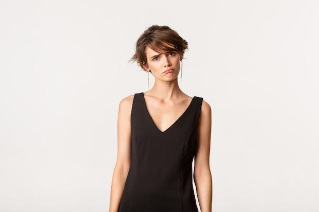 黒のドレスを着た悲しい臆病な少女が気分を害し、白に動揺している画像。