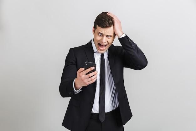 携帯電話を持って、彼の手で叫んでいるフォーマルなスーツを着た怖がっている白人ビジネスマンの画像は孤立していた