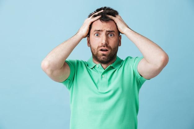 Изображение испуганного сбитого с толку молодого красивого бородатого мужчины, позирующего изолированно над синей стеной.