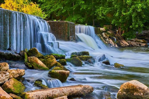 Изображение живописного пейзажа каскадных водопадов через искусственную плотину в мшистые скалы и реку