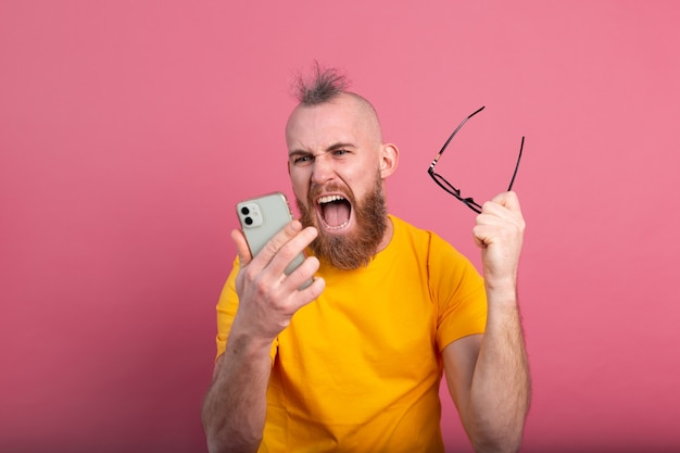 ピンクに非常に興奮して勝利と成功を祝う若いひげを生やしたハンサムな男の叫びの画像
