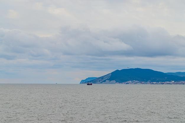 海と山の風景の画像。曇天。船が遠くを航行する