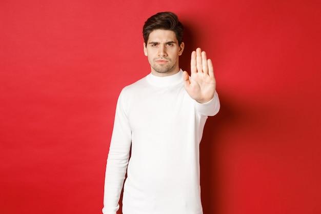 片手を伸ばす何かを禁止し、禁止するのをやめるように言っている真面目で自信のある男性の画像...