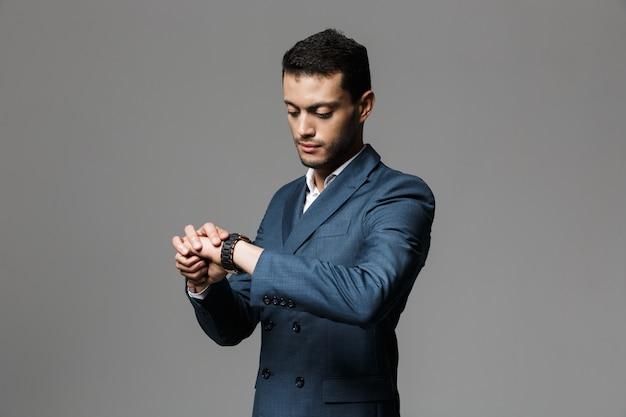 灰色の壁に隔離された腕時計を見てフォーマルなスーツを着た30代の深刻なアラビアのビジネスマンの画像