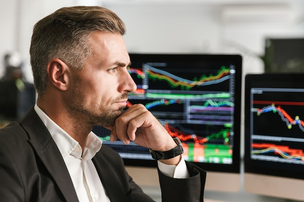Изображение серьезного бизнесмена 30-х годов в костюме, работающего в офисе на компьютере с графикой и диаграммами на экране