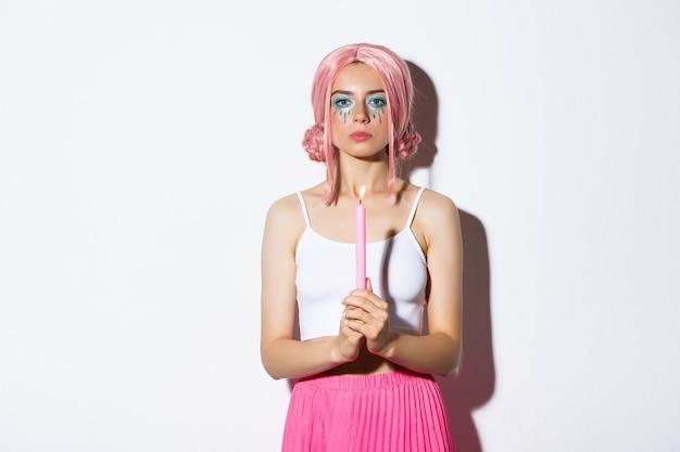 Изображение серьезной девушки одетой как фея на хэллоуин, держа свечу, стоя в розовом парике.