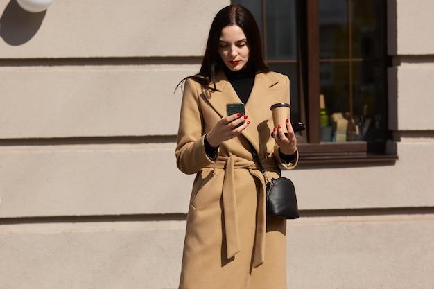 日当たりの良い街で彼女の電話を使用してエレガントなベージュのコートを着ている深刻な若い女性の画像