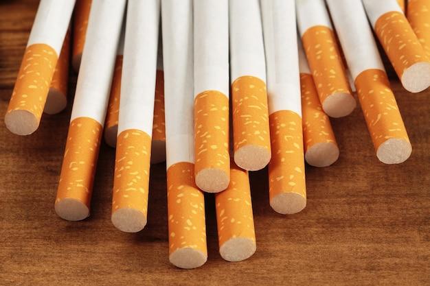 いくつかの市販のタバコの画像。木製にタバコを積みます。または禁煙キャンペーンのコンセプト、タバコ