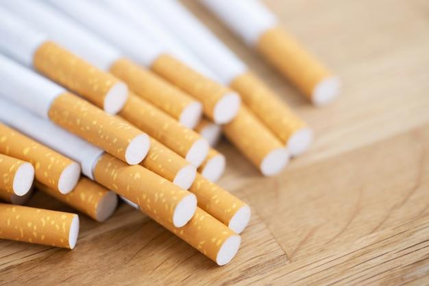 Изображение нескольких сигарет промышленного производства. куча сигарет стопки на деревянных. или концепция кампании по предотвращению курения, табак