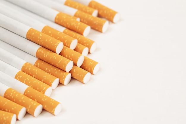 白い背景の上のいくつかの市販のパイルタバコの画像。または禁煙キャンペーンのコンセプト、タバコパターンの上面図。 Premium写真
