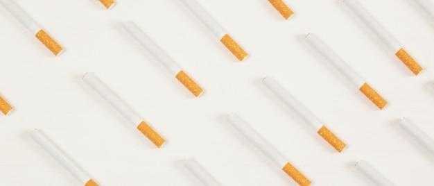 白い背景の上のいくつかの市販のパイルタバコの画像。または禁煙キャンペーンのコンセプト、タバコパターンの上面図。