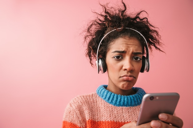 충격 된 불쾌 하 게 아름 다운 젊은 아프리카 여자의 이미지는 휴대 전화를 사용 하여 헤드폰으로 고립 된 듣는 음악을 포즈.