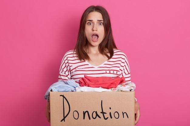 Изображение потрясенной эмоциональной леди с широко раскрытым ртом и глазами, удивляясь, имея в руках картонную коробку с подаренной одеждой, смотрит прямо в камеру. люди и волонтерство концепции.