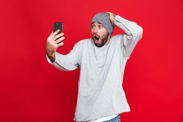 충격을받은 남자 30 대의 이미지가 머리를 잡고 서있는 동안 스마트 폰을 들고 격리 됨