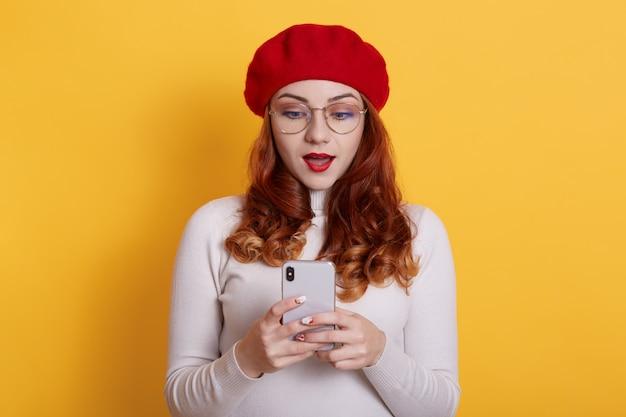 黄色の手で携帯電話でポーズをとって赤いベレー帽のショックを受けた学生の女の子の画像