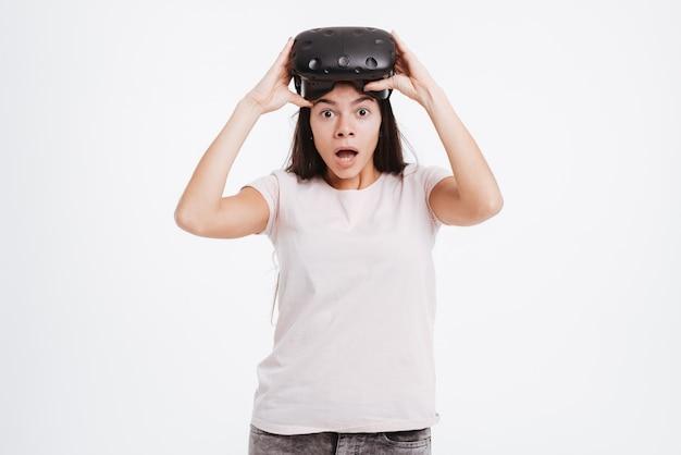 バーチャルリアリティデバイスを身に着けているショックを受けた若い女性の画像。正面を見てください。