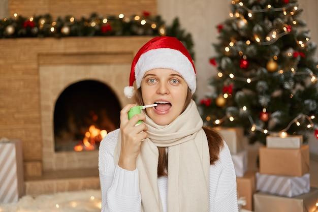 Изображение больной европейской женщины с широко открытым ртом, болит горло, страдает от приступа боли, носит вязаный свитер и шляпу санта-клауса, держит лекарство от горла, чтобы вылечиться.