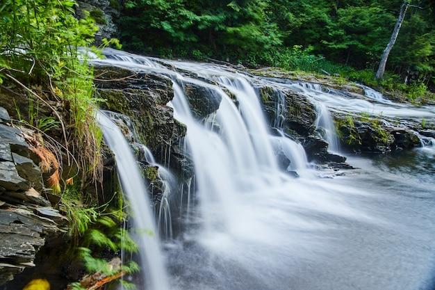 Изображение сбоку крупным планом на водопады, прорезающие скалы в лесу