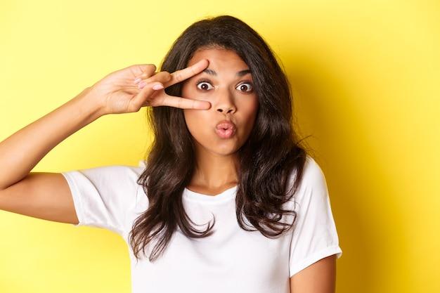 Изображение глупой и милой афроамериканской девушки-подростка, показывающей знак мира и надутой на поцелуй, стоящей на желтом фоне