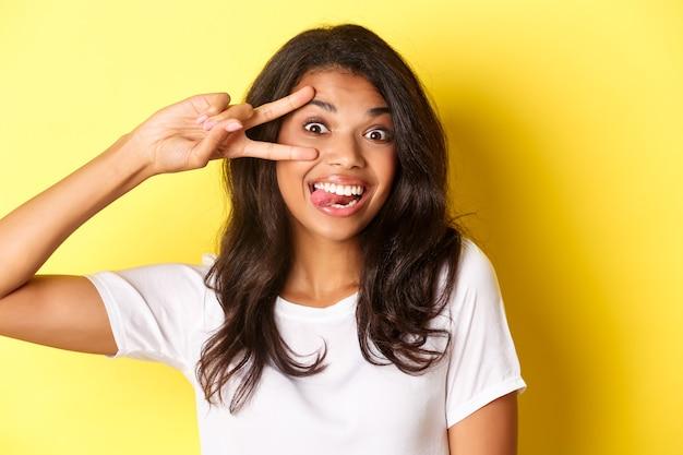 Изображение глупой и милой афроамериканской девочки-подростка, показывающей знак мира и улыбающейся, стоящей на желтом фоне