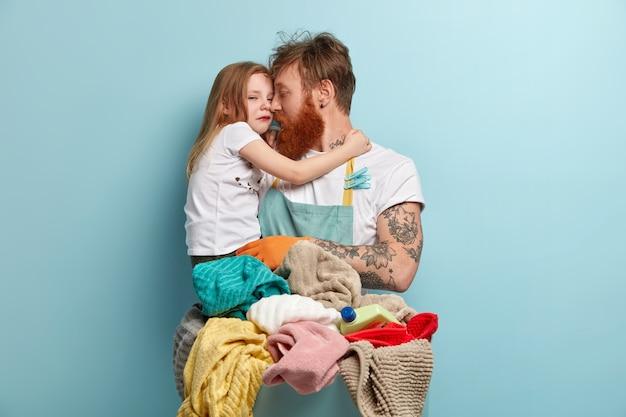シングルファーザーが泣いている小さな娘を抱いている画像