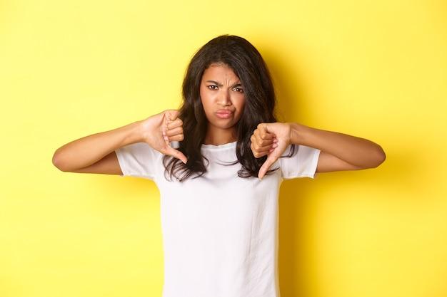 Изображение скептически настроенной, невеселой милой афро-американской девушки, показывающей палец вниз и гримасой, оценивающей что-то плохое, разочарованной стоящей на желтом фоне.
