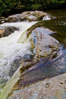 Изображение небольшого водопада, спускающегося по скалам в реку с белой водой