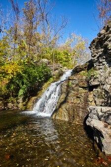 Изображение небольшого водопада над скалами в пруд падает
