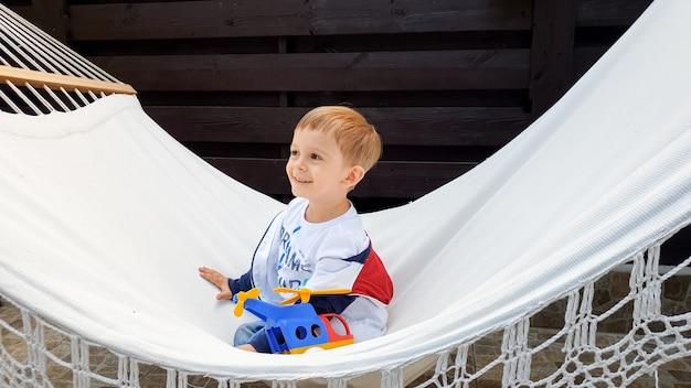 스윙과 집 뒷마당에서 해먹에 누워 웃는 사랑스러운 유아 소년의 이미지