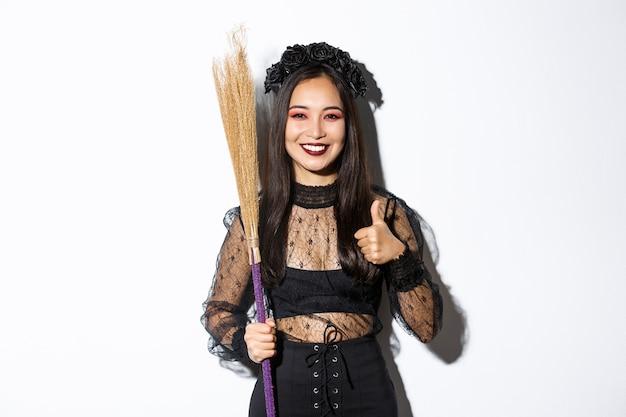 ほうきで魔女の衣装を着て、白い背景の上に立って、承認の親指を示す、笑顔のアジアの女性の画像。
