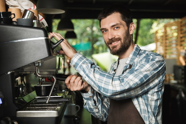屋外のカフェや喫茶店で働いているときにコーヒーを作るエプロンを着て笑顔のバリスタ男性の画像