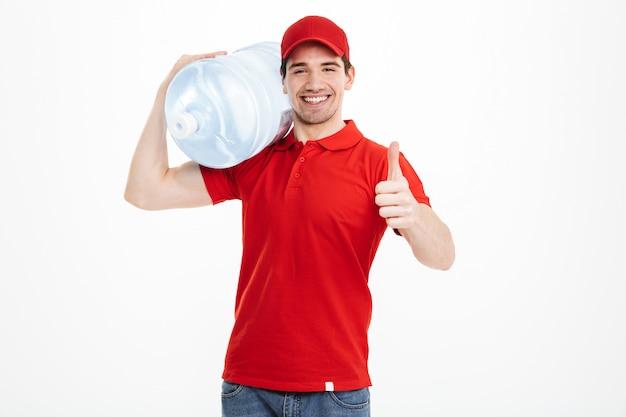 Изображение улыбается курьер доставки бутилированной воды в красной футболке и кепке, перевозящих бак свежего напитка и показывая большой палец вверх, изолированных на пустое пространство