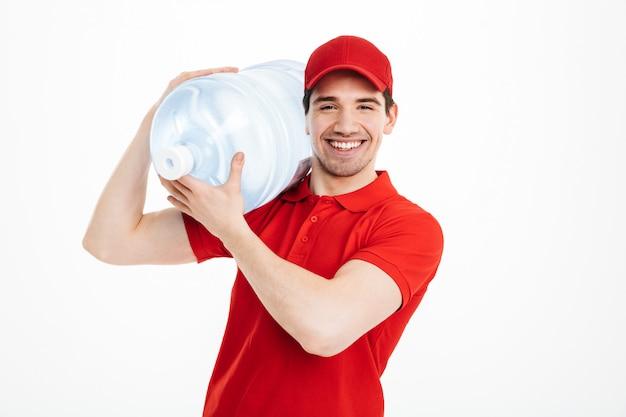 Изображение улыбается курьер доставки бутилированной воды в красной футболке и кепке, перевозящих бак свежего напитка, изолированных на пустое пространство