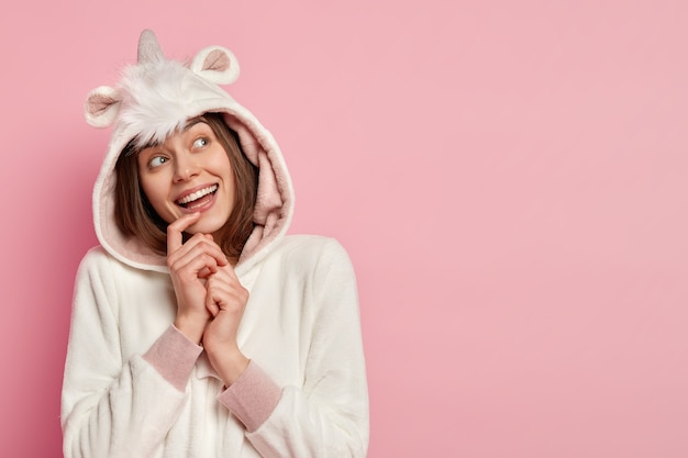 Изображение улыбающейся девушки с веселым мечтательным выражением лица, надежды на исполнение мечты, позитивная улыбка, в домашнем костюме кигуруми, позирует на розовой стене, свободное место для вашей рекламы