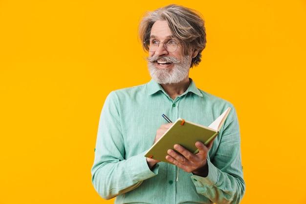 Изображение улыбающегося седовласого бородатого мужчины в голубой рубашке, позирующем изолированно на желтой стене, написание заметок в тетради.
