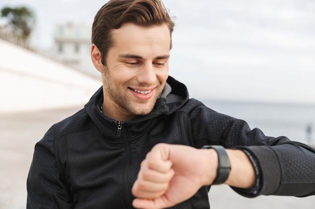 해변에서 산책로에 앉아있는 동안 손목 시계를보고 검은 운동복을 입은 30 대 웃는 남자의 이미지
