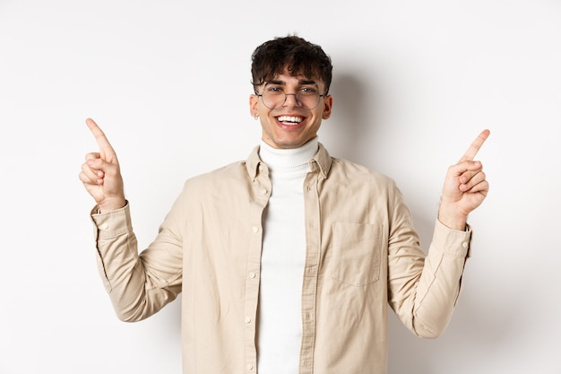 横向きの指を指し、広告や変種を表示し、白い背景の上に陽気に立っている眼鏡でハンサムな男の笑顔の画像