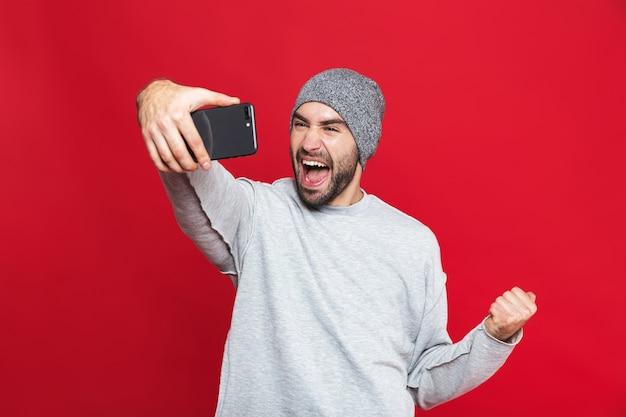 Изображение улыбающегося человека 30-х годов, держащего смартфон и делающего селфи, изолированные
