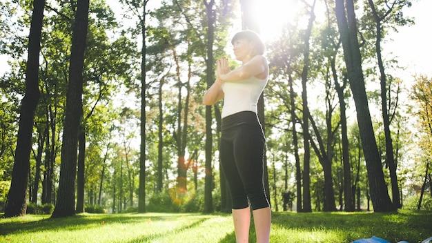 ストレッチやヨガの練習をしているフィットネス服を着た笑顔の中年女性の画像。公園の芝生の上のフィットネスマットで瞑想とスポーツをしている女性